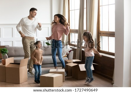 Happy family with two little daughters celebrating moving day, excited by relocation into new house, laughing mother and father with children jumping in living room with cardboard boxes Сток-фото ©