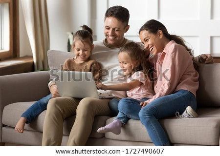 Happy family with two little daughters using laptop together, sitting on cozy sofa at home, smiling father and mother with preschool girls sisters looking at computer screen, shopping online