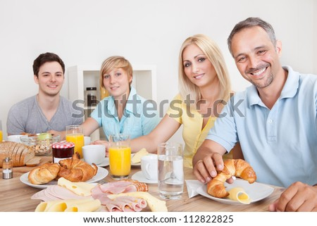 Happy family with two teenage children sitting around the table enjoying a healthy breakfast - stock photo