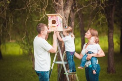 Happy family with Wooden birdhouse on tree in summer green forest
