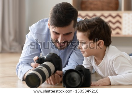 Happy family young dad and cute little son holding modern digital cameras playing on warm floor at home, father photographer showing photos teaching small preschool child boy having fun bonding