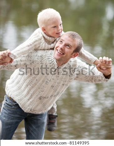 happy  family; young father and his five year old son near the lake outdoor on a summer day (focus on the man)