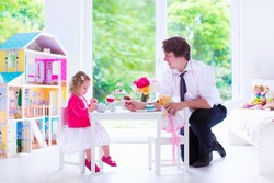 Happy family, young father and his little daughter, cute curly toddler girl wearing a dress, playing together with doll house, having toy tea party in a white sunny nursery