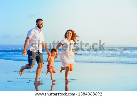 Happy family - young father, mother, baby son run together, child jump with fun by water pool along sunset sea surf on tropical beach. Travel lifestyle, people walking with kid on summer vacation