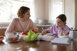 Happy family young mother and teenage daughter studying, eating together at home. Adult parent mum preparing vegetable salad helping tween school girl child doing homework sitting at kitchen table.