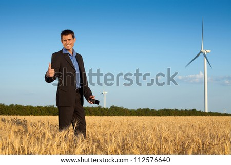 happy farmer (businessman) standing in wheat field over wind turbines background and showing ok (thumbs up)