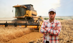 Happy farmer proudly standing in a field with arms crossed on chest. Combine harvester driver going to crop rich wheat harvest. Agronomist wearing flannel shirt, looking at camera on a farmland.