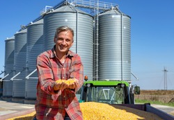 Happy Farmer Showing Freshly Harvested Corn Grains Against Grain Silos. Farmer with Corn Kernels in His Hands Sitting in Trailer Full of Corn Seeds. Farmer's Hands Holding Harvested Grain Corn.