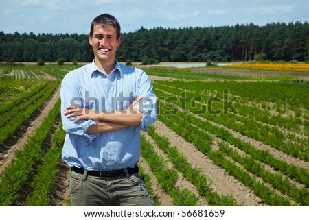 Happy farmer with arms crossed in front of his fields