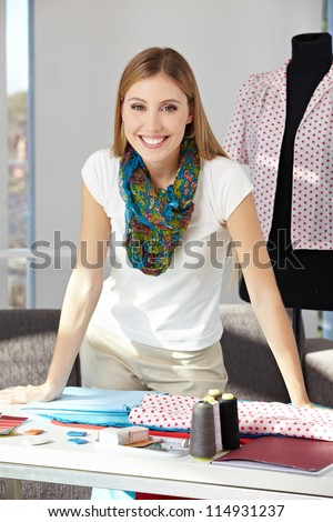 Happy fashion designer standing in her office with dress form