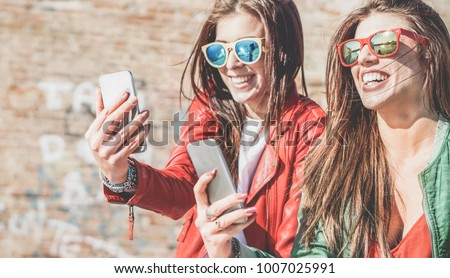 Happy fashion friends watching videos on smartphone - Girlfriends having fun social technology trends outdoors - Friendship, youth lifestyle, millennials generation and tech concept #1007025991