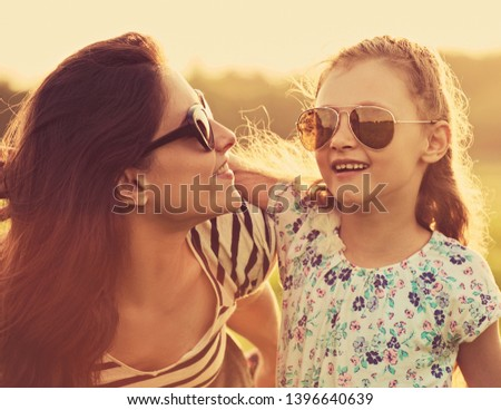 Happy fashion kid girl embracing her mother in trendy sunglasses and looking each other with love on nature background. Closeup portrait of happiness.  #1396640639