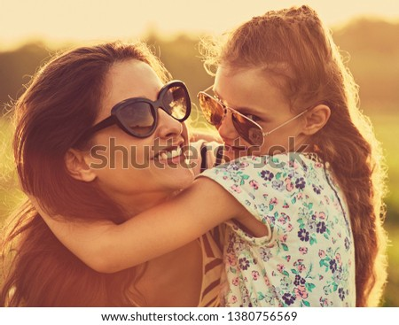 Happy fashion kid girl embracing her mother with strong love in trendy sunglasses smiling and looking on nature background. Closeup toned portrait #1380756569