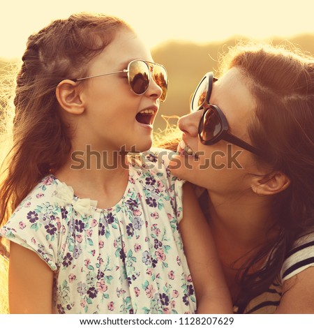 Happy fashion kid girl speaking to her mother in trendy sunglasses on nature sunset background. Closeup portrait of happiness. #1128207629