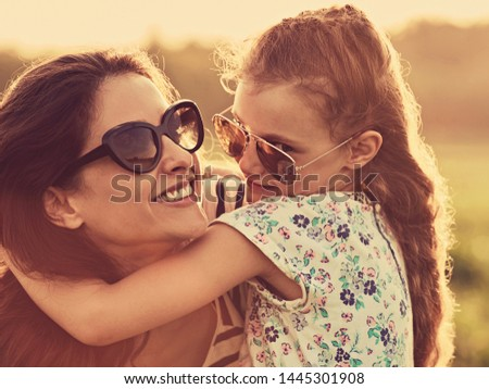 Happy fashion mother embracing  her playful mischievous daughter in trendy sunglasses on nature summer background. Closeup toned portrait #1445301908