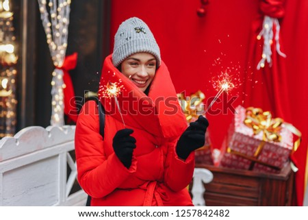 Happy fashion woman hold in hands bengal lights which sparkle. Red down jacket and christmas mood. New year and christmas holiday, winter concept