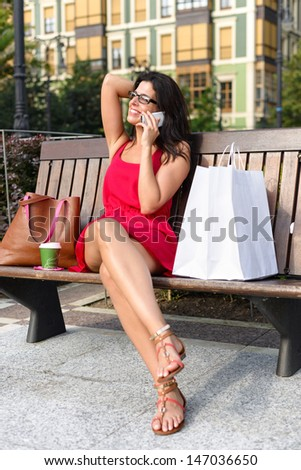 Happy fashion woman taking a break after shopping in the sales and calling by cell phone. Beautiful brunette girl sitting on a bench with white bags in european city square.