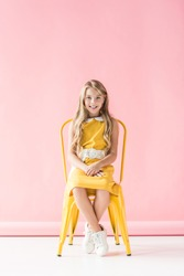 happy fashionable adorable youngster sitting on yellow chair on pink