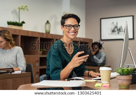 Happy fashionable girl using smartphone while working on desktop computer. Cheerful young business woman sitting in coworking space  and looking at camera. Portrait of  freelancer with eyeglasses.