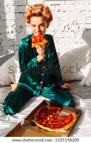 happy fashionable woman in silk pajama eating pizza in bed in bedroom interior