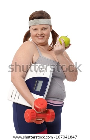 Happy fat woman eating green apple, holding dumbbells and scale in sportswear.