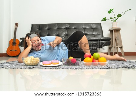 Happy fat woman laying down and eating sweet ice cream before popcorn, fruits and donuts. Overweight female happy with big meal. Concept when you work from home. Body transformation after lockdown. Photo stock ©