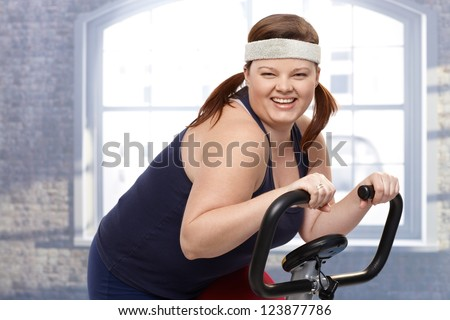 Happy fat woman training on exercise bike, smiling.