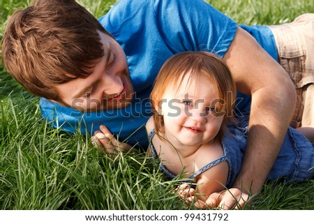 Happy Father And Daughter Laying In Grass