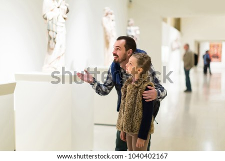 happy father and daughter looking at ancient bas-reliefs in museum