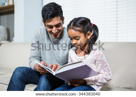 Happy father and daughter using laptop on the sofa in living room
