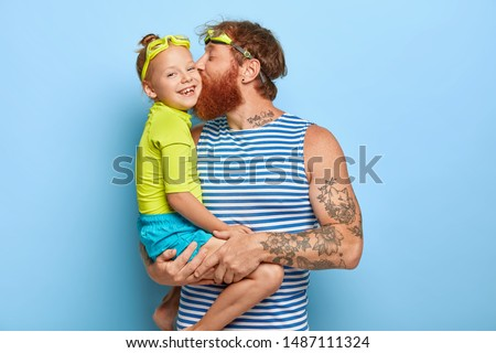 Happy father and daughter wear goggles and summer clothes, have fun together during rest. Affectionate dad carries litle girl, kisses her in cheek, expresses love. Family and recreation concept