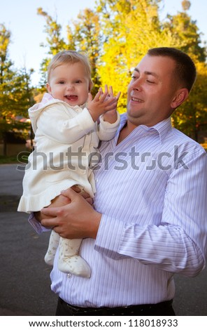 Happy father and his baby daughter having fun in the park