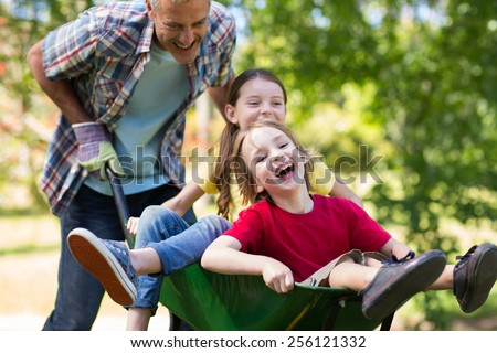 Happy father and his children playing with a wheelbarrow on a sunny day Stock fotó ©