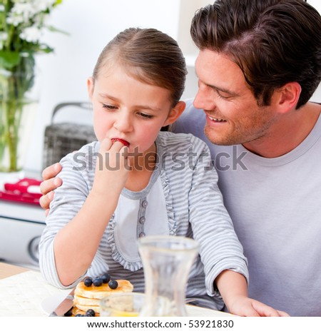 Happy father and his daughter having breakfast together in the kitchen #53921830