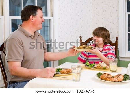 Happy father and his teenage son eating at the dinner table