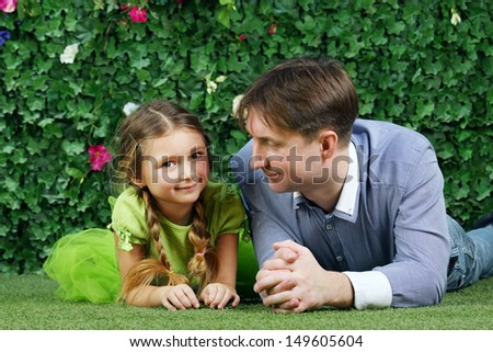 Happy father and little daughter lie on grass near hedge with flowers in garden.
