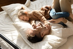 Happy father and little daughter relaxing in cozy bed together, smiling dad having fun with cute preschool girl, resting, taking nap in bedroom, family spending weekend together, enjoying free time