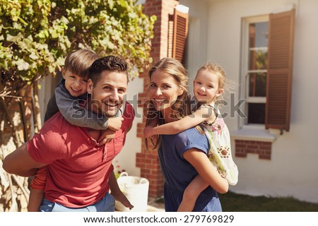 Happy father and mother looking at camera while piggybacking their son and daughter. Happy young family of four playing in their backyard on a sunny day.