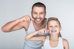 happy father and son brushing teeth and looking at camera together isolated on grey