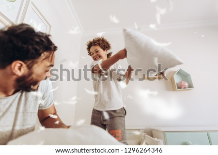 Happy father and son having a pillow fight on bed with feathers flying around. Father and son having fun playing at home.