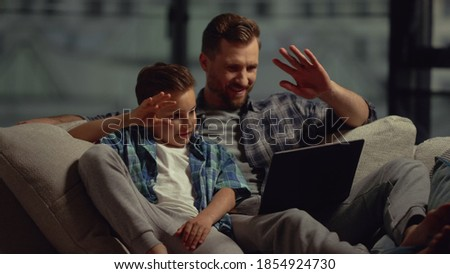 Happy father and son having video call via computer indoors. Cheerful dad and kid boy waving hands to caller on laptop at home. Smiling man and child looking netbook screen on couch.