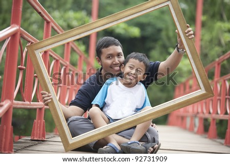 Happy father and son holding a frame on a bridge