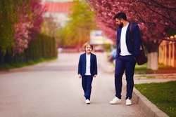 happy father and son in suits walking along the spring street