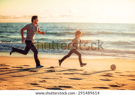 Happy father and son play soccer or football on the beach on sunset having great family time on summer holidays. Lifestyle, vacation, happiness, joy concept