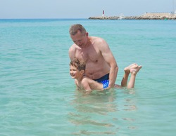 Happy father and son playing in the water. Father teaches son to swim.