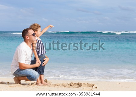Happy father and son playing on the beach at the day time. Concept of friendly family.