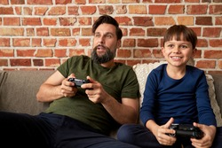 Happy father and son playing video game on couch
