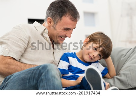 Happy Father And Son Sitting On Couch Enjoying