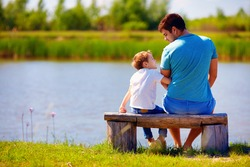 happy father and son sitting on the river bank