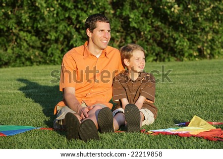 happy father and son sitting together at the park with kites